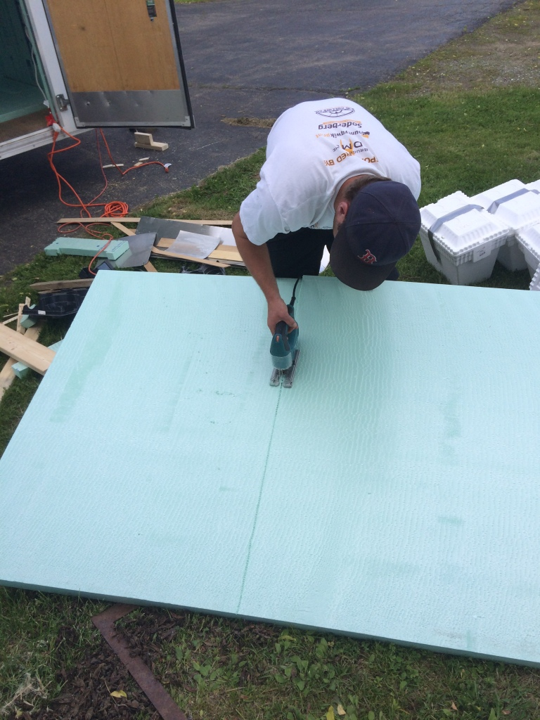 Cutting insulation to line the trailer